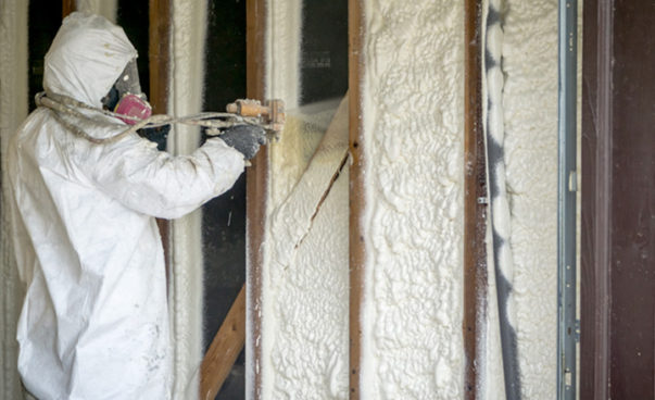 Insulation being sprayed on walls